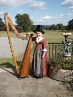 Photograph of Lady Llanover's Great-Great-Great-Great Grand-Daughter wearing her ancestors original costume with a Llanover Triple Harp
